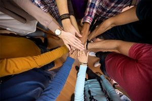people-standing-in-circle-with-hands-in-center